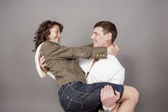 Happy Caucasian Couple Standing Embraced Together. Against Gray Stock Image