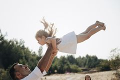 Happy caucasian dad and his little daughter having fun. Father throws sweet daughter in white dress in the air. stock photo