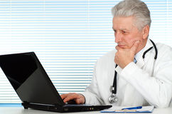 Happy Caucasian doctor with a laptop sitting Stock Photo