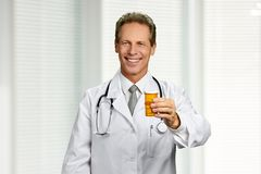 Happy caucasian doctor showing pills. Smiling medical worker holding medication and looking at camera. Medicine, pharmacy, treatment stock photography