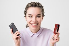 Happy caucasian european young woman holding phone and card making order online. Royalty Free Stock Photo