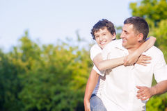 Happy Caucasian Family of Father and Son Piggybacking Outdoors. Against Nature Green Forest. Royalty Free Stock Photography
