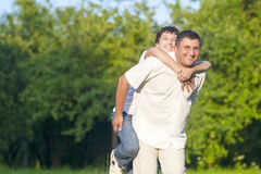 Happy Caucasian Family of Father and Son Piggybacking Outdoors Royalty Free Stock Photo