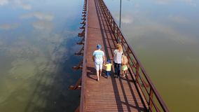 Happy caucasian family holding hands walking wooden bridge over lake water stock video