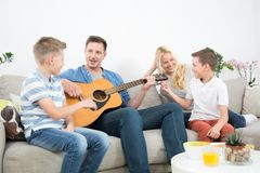 Happy caucasian family smiling, playing guitar and singing songs together at cosy modern home. Happy caucasian family smiling while playing guitar and singing royalty free stock image