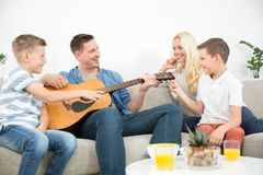 Happy caucasian family smiling, playing guitar and singing songs together at cosy modern home. Happy caucasian family smiling while playing guitar and singing royalty free stock photo