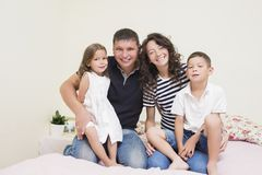 Happy caucasian Family of Two Parent and Two Kids Sitting Together. Family Ideas. Happy caucasian Family of Two Parent and Two Kids Sitting Together Embraced and Royalty Free Stock Photography