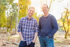 Happy Caucasian Father and Son Portrait Outdoors. Handsome Caucasian Father and Son Pose for a Portrait Outdoors stock image