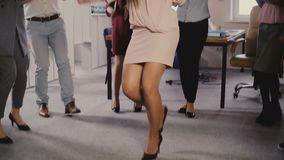 Happy Caucasian female executive doing funny victory dance. Mixed race colleagues celebrate business success together 4K