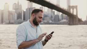 Happy Caucasian freelance entrepreneur typing message on smartphone, smiling near Brooklyn Bridge New York City 4K. Happy Caucasian freelance entrepreneur stock video footage