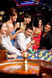 Happy caucasian friends playing roulette in casino stock photo
