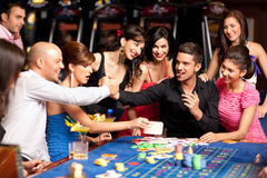 Happy caucasian friends playing roulette in casino Royalty Free Stock Photography