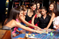 Happy caucasian friends playing roulette in casino Royalty Free Stock Images