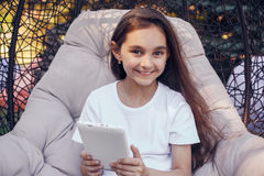 Happy caucasian girl holding white  tablet PC, sitting in a park Stock Photos