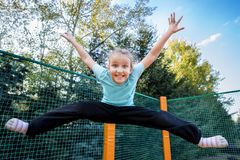 Girl Trampoline Jump. Happy caucasian girl jumping high on a trampoline on a sunny day outdoors Royalty Free Stock Images