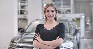 Happy Caucasian girl posing at the background of blurred black automobile. Young smiling woman buying or leesing car in