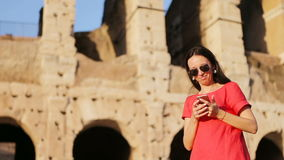 Happy caucasian girl talks by cell phone in front of most popular destination in the world Colosseum in Rome, Italy stock video footage