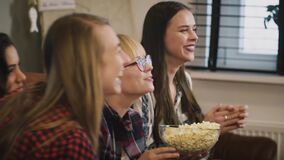 Happy Caucasian girls watch TV show. Slow motion. Emotion. Beautiful ladies watching sports game with popcorn at home. stock video