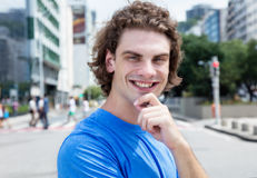 Happy caucasian guy with long hair in the city. Happy caucasian guy with long hair looking at camera outdoor in the city Royalty Free Stock Photography