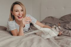 Happy Caucasian laughing smiling blonde woman lying on bed in bedroom at home and playing with oriental point-colored cat royalty free stock photography