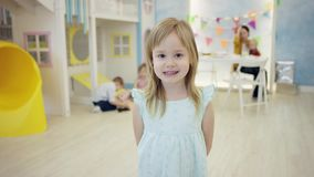 Happy little girl is smiling and posing in front of the camera with other kids and adult woman on a background in a room stock video footage