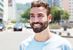 Happy caucasian man with beard outdoor in city. With streets and buildings in the background Stock Image