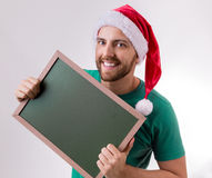 Happy caucasian man with the christmas hat holding a blackboard Royalty Free Stock Photo