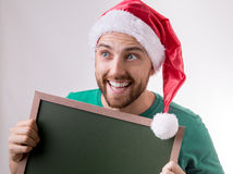 Happy caucasian man with the christmas hat holding a blackboard Royalty Free Stock Photos
