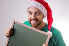 Happy caucasian man with the christmas hat holding a blackboard Stock Photography