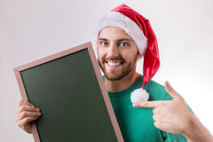 Happy caucasian man with the christmas hat holding a blackboard Royalty Free Stock Photography