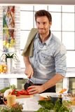 Happy caucasian man cooking in kitchen at home stock photos