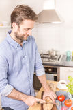 Happy caucasian man cutting bread roll in the kitchen - breakfas Royalty Free Stock Image