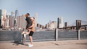 Happy Caucasian man meeting his girlfriend, hugging and smiling at sunny Manhattan skyline in New York City slow motion.