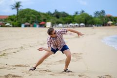 Happy caucasian man playing on beach throwing stones on ocean, Bali. Indonesia, outdoor Royalty Free Stock Photo
