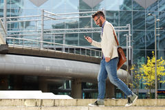 Happy caucasian man walking outdoors and reading text message Royalty Free Stock Photo