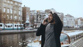 Happy Caucasian man walks and talks on the phone. 4K. Excited creative tourist sharing emotions in Amsterdam old town. Picturesque crowded river embankment stock footage