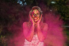 Happy caucasian model with curly hair standing n a cloud of pink. Happy caucasian woman with curly hair standing n a cloud of pink dry paint, celebrating Holi royalty free stock image