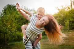 Happy Caucasian mother and son outdoors in park on sunny spring day. Young brunette mother lifting her son in park having fun enjoying motherhood. Square stock photos
