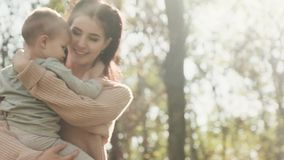 Young mother is spinning with her son in her arms in autumn park