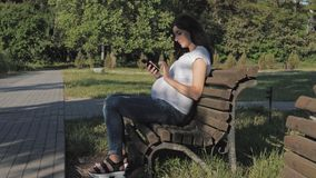 Beautiful pregnant woman sits on a park bench and uses a smartphone apps. Happy caucasian pregnant brunette woman sitting on park bench on summer sunny day stock video