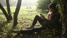 Happy caucasian pretty woman sending sms texting in the autumn park. stock video footage