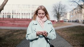 Happy Caucasian 30s woman typing on smartphone. Pretty stylish blonde texting while walking in the city. Slow motion. Happy Caucasian 30s woman typing on stock video footage
