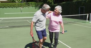 Happy caucasian senior couple embracing on outdoor tennis court in sun after playing a game