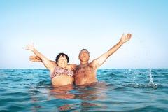 A happy caucasian senior couple enjoys their sea vacation on the stock photography