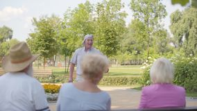 Happy caucasian senior man dancing in front of his friends sitting at the bench. Positive old guy entertaining mature. Company in the summer park. Group of stock footage