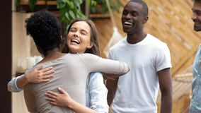 Happy caucasian teen girl embracing african friend at group meeting royalty free stock photo