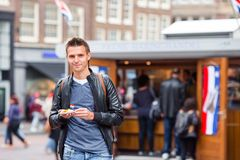 Happy caucasian tourist with fresh herring with onion and netherland flag in Amsterdam. Traditional dutch food outdoor. Traditional dutch food: herring fish with royalty free stock photos