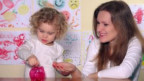 Happy caucasian woman and child girl putting coins into piggy bank. On table. Static shot. 4K UHD stock video footage