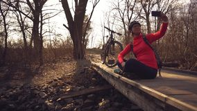 Happy caucasian woman cyclist makes a photo of herself a selfie on the phone while sitting on the bridge over a river in. The forest in sunny weather stock footage