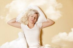 Happy Caucasian woman enjoying in good sleep. Sleeping in clouds stock photography